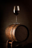 Wine on barrel. Wineglass with red wine on a wooden barrel stock image