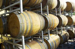 Wine Barrels. Stacked on metal shelves outdoors Stock Images