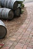 Wine barrels and brick path. Cropped view of a walking path near a vineyard. Decorative wine casks line the pathway Stock Photography