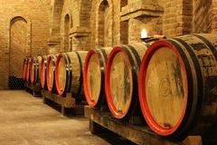 Wine barrels in cellar. Wine barrels and bottles in a cellar royalty free stock photos