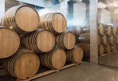 Wine barrels stacked in the basement cellar of a winery Stock Image