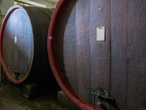 Wine barrels stacked in the old cellar of the winery close up. Stock Photography