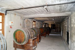 Wine barrels stacked in the old cellar of the winery. Royalty Free Stock Photos