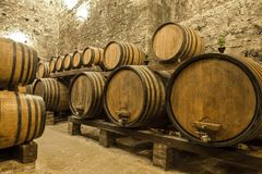 Wine barrels stacked in the old cellar of the winery Stock Photography