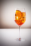 Wine-based long drink. Glass of exotic drink, wine-based; mixed drink with aperol, prossecco wine, soda, ice cubes Royalty Free Stock Image
