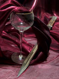 Wine and bayonet. Broken wineglass from crystal and bayonet among dark red tissue royalty free stock photo