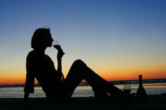 Wine on the beach. Young girl drinking wine on the beach stock image