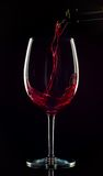 Wine being poured. Dark background for atmosphere, wine caught by the light is dark red Stock Photos