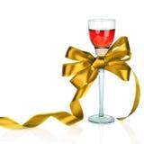 Wine in bicchiere di vino e nell'arco dorato del regalo del raso, su bianco Fotografia Stock