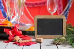 Wine and  blackboard. Bottle of wine and decorations next to empty blackboard for your text on wooden table. Christmas or New Year`s drink Royalty Free Stock Photos