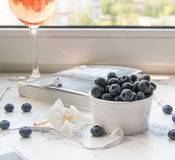 Wine and blueberries. A glass of pink wine and a cup of blueberries on white table Royalty Free Stock Photo