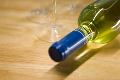 Wine Bottle. Unopened wine bottle and glasses on a wooden table Royalty Free Stock Photography
