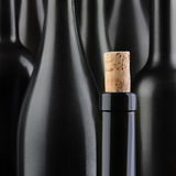 Wine Bottle Abstract. Closeup of a wine bottle with the cork partially out, in front of an out of focus group of larger bottles. Selective focus and color Stock Image