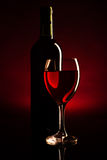 Wine Bottle And Glass Silhouette Over Dark Red Royalty Free Stock Images