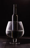 Wine bottle in the big wine glass isolated Stock Image
