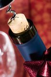 Wine bottle cork almost out. Closeup of red wine bottle neck with cork almost out and holiday ribbon Stock Images