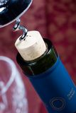 Wine bottle cork almost out. Closeup of red wine bottle neck with cork almost out and glass out of focus Stock Photography