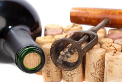 Wine Bottle with Corkscrew. Older corkscrew lies on some corks beside a wine bottle Stock Images
