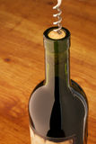 Wine bottle with corkscrew. On brown wood surface. Selective focus on top bottle Royalty Free Stock Image