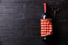 Wine bottle and corkscrew on Burned wooden background Stock Photo