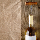 Wine bottle with corkscrew on wood Royalty Free Stock Image
