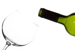 Wine bottle and an empty glass against white backg Royalty Free Stock Images