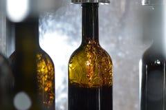 Wine bottle filling along conveyor belt in bottling factory. Wine bottle filling along a conveyor belt in a wine bottling factory Royalty Free Stock Images