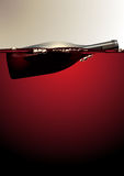 Wine bottle floating on red wine Stock Images