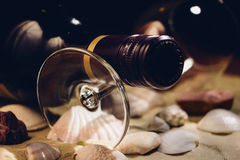 Wine Bottle and Glas on Shells - Film effect. An unopened bottle of red wine resting on a glass on sand and shells. Film look, grain effect Stock Photo