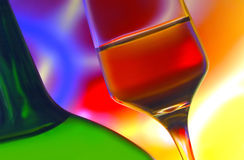 Wine bottle and glass. Tilted view of a wine bottle and glass with vibrant abstract background stock image