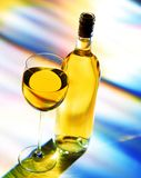 Wine Bottle and Glass. Glass of white wine and bottle on a colorful background stock images