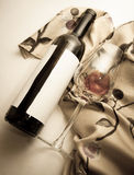 Wine bottle and glass on beige drapery Stock Photos