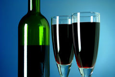 Wine bottle and glass on a blue background Stock Image