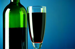 Wine bottle and glass on a blue background Stock Images