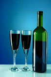 Wine bottle and glass on a blue background Royalty Free Stock Photos