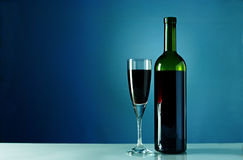 Wine bottle and glass on a blue background Royalty Free Stock Images