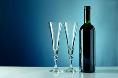 Wine bottle and glass on a blue background Royalty Free Stock Image