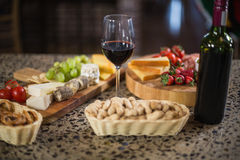 Wine bottle with a glass and a buch of food Stock Photography