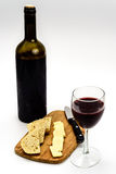 Wine Bottle with Glass Cheese Bread Cutting Board. Wine bottle with one glass, cheese, bread and knife on a bamboo cutting board Royalty Free Stock Photo