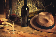 Wine bottle, glass, grape and hat. On a table Stock Image