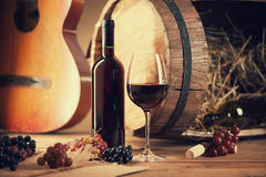 Wine bottle, glass, grapes, barrel and guitar. Photography of a wine bottle, glass, grapes, barrel and guitar Stock Images