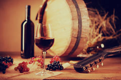 Wine bottle, glass, grapes, barrel and guitar. On a table Stock Photo