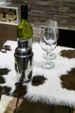 Wine bottle with glass next to silver cocoktail shaker on table. Decorated with fur in private zone Royalty Free Stock Photo