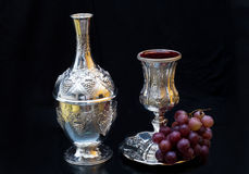 Wine bottle and a glass of pure silver with grapes. Black background Stock Photos
