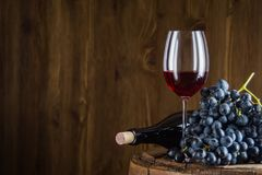 Wine bottle, glass of red wine and grape. Still life of red wine with wooden keg. Wine bottle, glass of red wine and grape on a old wooden barrel. Wine tasting Royalty Free Stock Photos