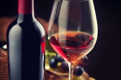 Wine. Bottle and glass of red wine with ripe grapes over black stock images