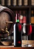 Wine bottle and glass of red wine on wooden cask. Wine shelves at the background. ÑŽ stock image