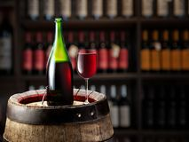 Wine bottle and glass of red wine on wooden cask. Wine shelves at the background.  stock images