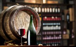 Wine bottle and glass of red wine on wooden cask. Wine shelves at the background.  royalty free stock image