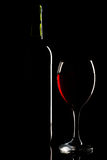 Wine bottle and glass silhouette over black Stock Images